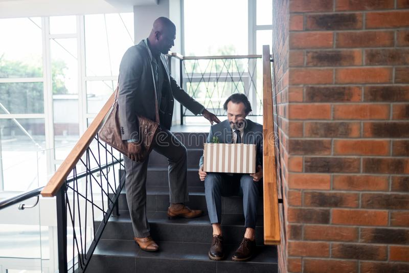 Homem de pele escura que acalma para baixo seu colega após a destituição fotografia de stock royalty free