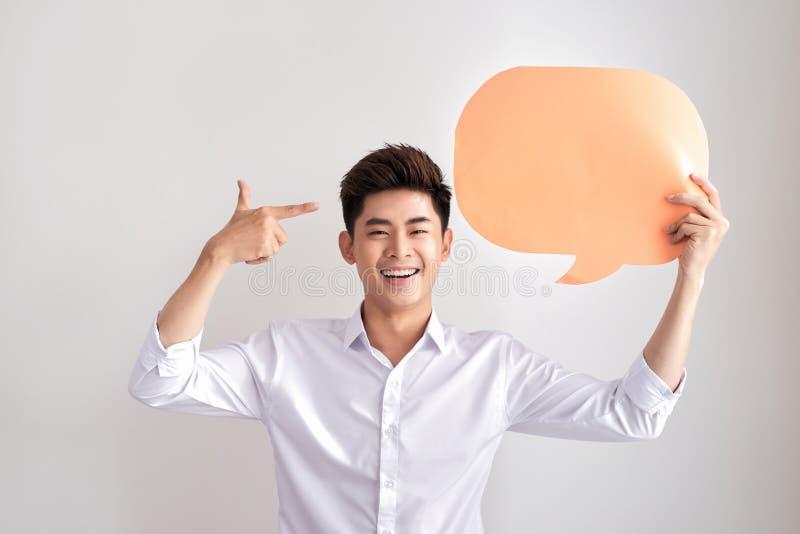 Homem de pensamento alegre que guarda o balão de discurso vazio branco com espaço para o texto isolado no fundo branco fotografia de stock