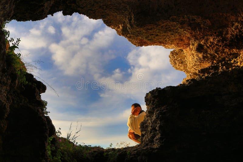 Homem de relaxamento do céu do furo da caverna imagem de stock royalty free