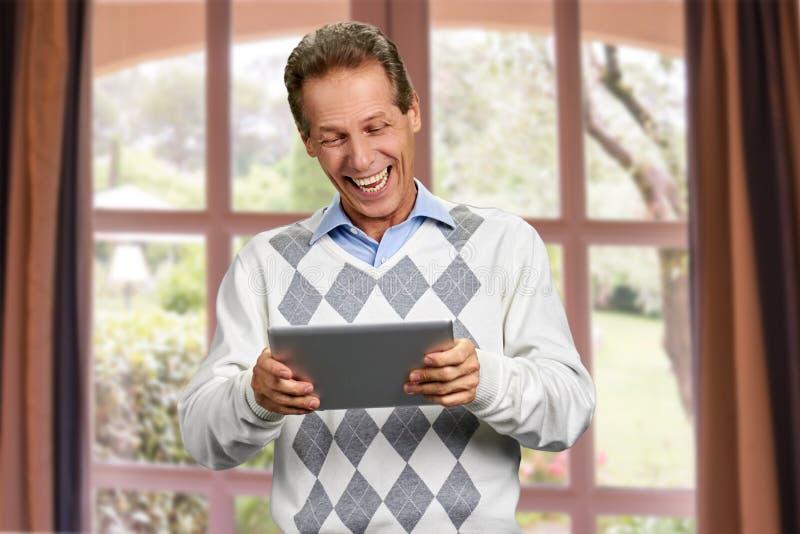 Homem de riso com tabuleta do PC fotografia de stock