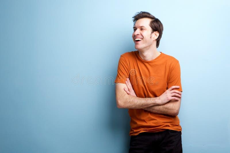 Homem de riso despreocupado cândido que está pela parede imagem de stock royalty free