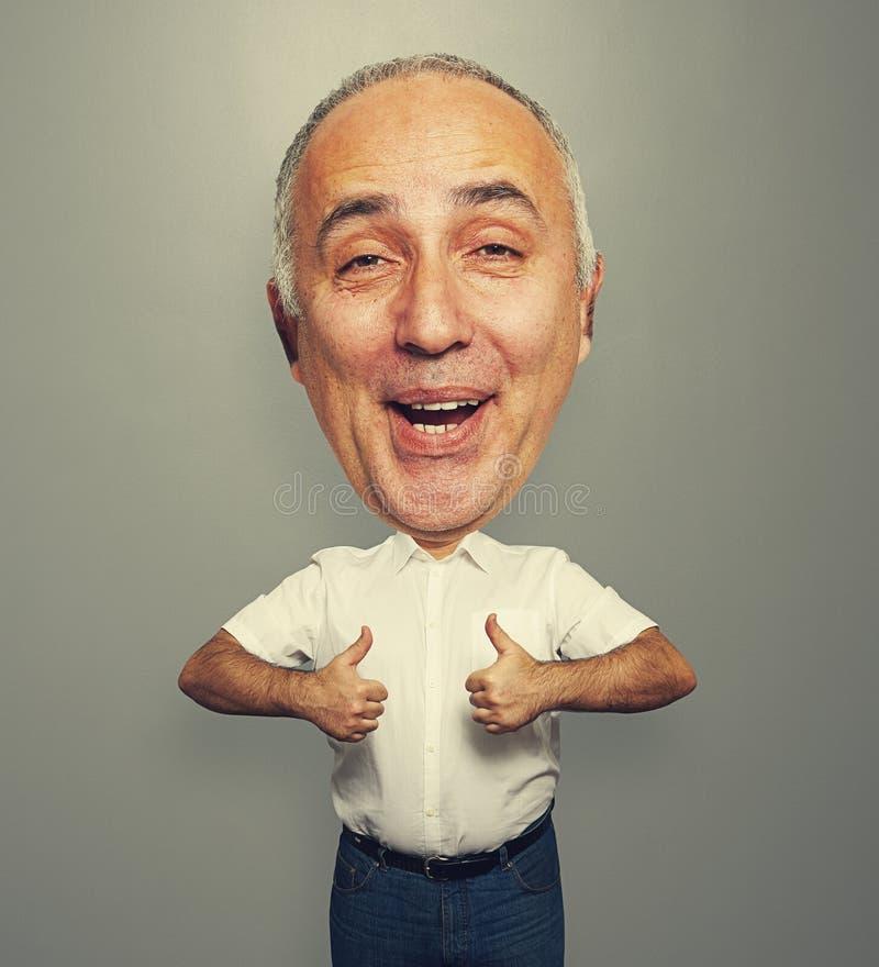 Homem de riso engraçado que mostra os polegares acima fotografia de stock
