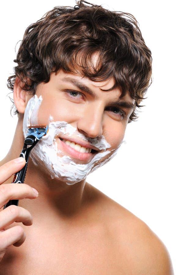 Homem de riso feliz que raspa sua face fotografia de stock
