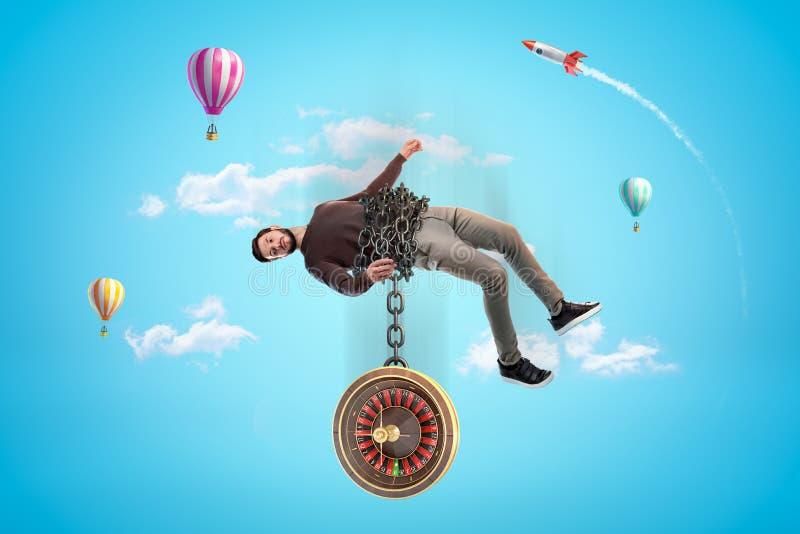 Homem de roupa casual acorrentado a roleta com balões de ar quente e foguete de espaço vermelho prateado no ar em azul fotos de stock royalty free