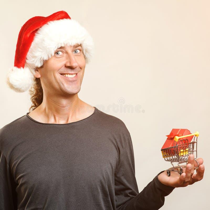 Homem de Santa Claus com pouco carro de compra do trole com presente Conceito das vendas e da compra do Natal Homem novo feliz no imagem de stock royalty free