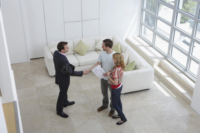 Homem de Shaking Hands With do mediador imobiliário pela mulher na casa nova fotografia de stock