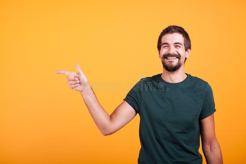 Homem de sorriso alegre que aponta em seu direito no copyspace foto de stock