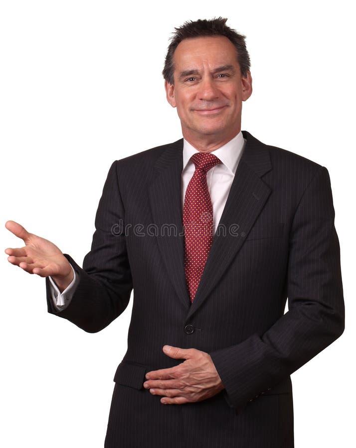 Homem de sorriso atrativo no terno que gesticula a boa vinda imagens de stock royalty free