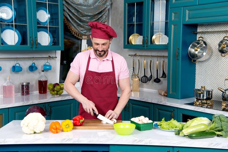 Homem de sorriso calmo que corta vegetais ao estar sozinho fotos de stock royalty free