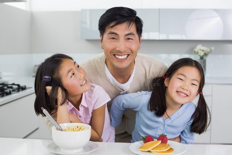 Homem de sorriso com as duas filhas felizes que comem o café da manhã na cozinha foto de stock