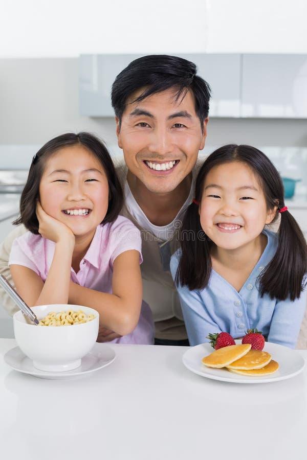 Homem de sorriso com as duas filhas que comem o café da manhã na cozinha fotos de stock royalty free