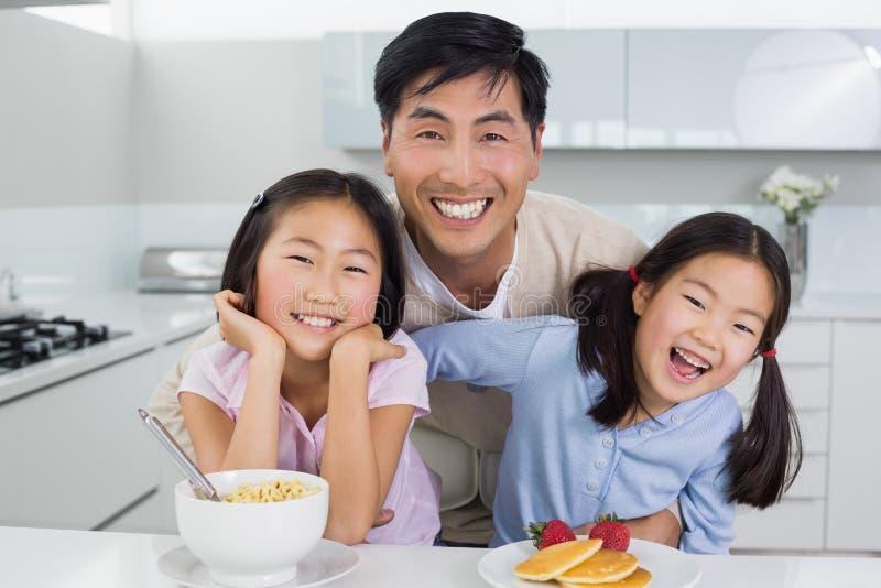 Homem de sorriso com as filhas felizes que comem o café da manhã na cozinha fotografia de stock