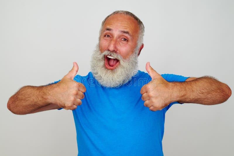 Homem de sorriso com a barba branca que dá dois polegares acima imagem de stock royalty free