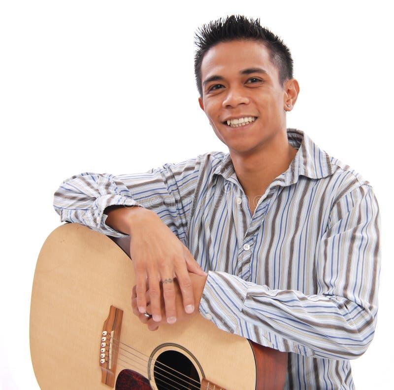 Homem de sorriso com guitarra fotografia de stock royalty free