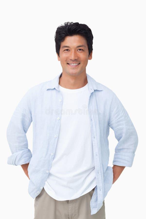 Homem de sorriso com mãos em seus bolsos fotografia de stock