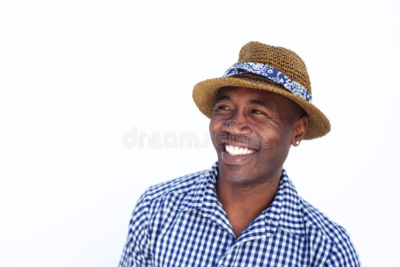 Homem de sorriso com o chapéu que olha afastado contra o fundo branco foto de stock