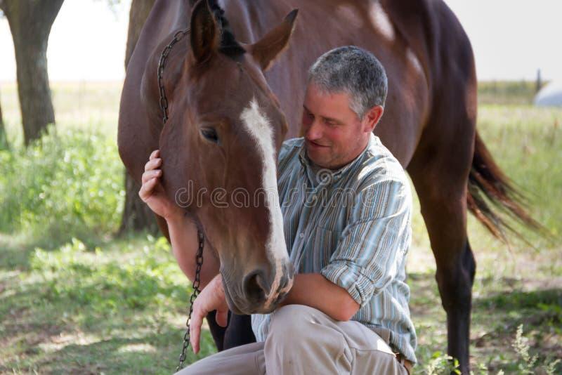 Homem de sorriso com seu cavalo no campo de Argentina imagens de stock