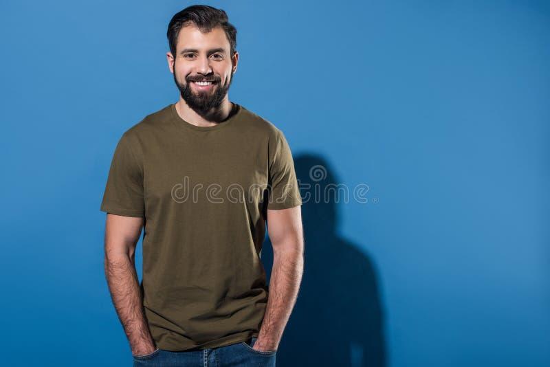 homem de sorriso considerável que está com mãos em uns bolsos imagem de stock