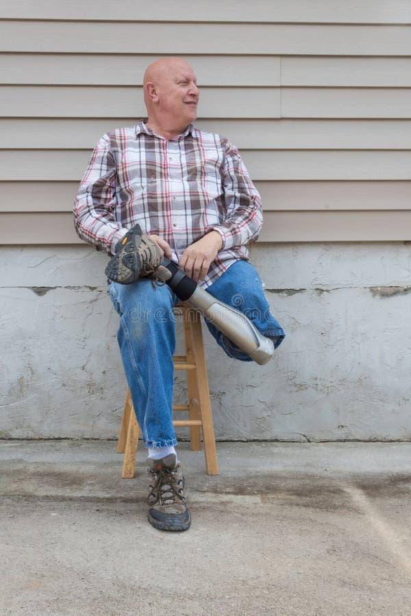 Homem de sorriso do amputado que senta-se em um tamborete, guardando o pé protético cruzado no tornozelo fotografia de stock