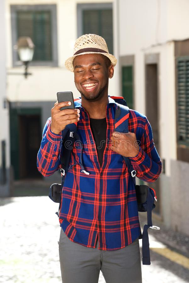 Homem de sorriso do curso com trouxa e telefone celular imagens de stock royalty free