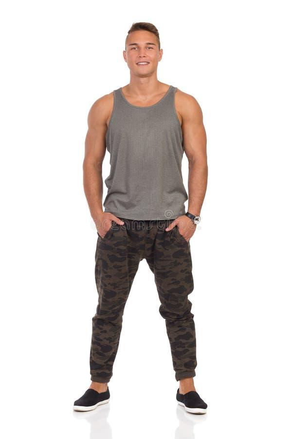 Homem de sorriso em calças de Gray Tank Top And Camo fotografia de stock royalty free