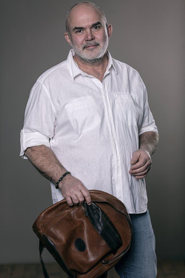 Homem de sorriso grisalho calvo idoso com uma trouxa imagem de stock