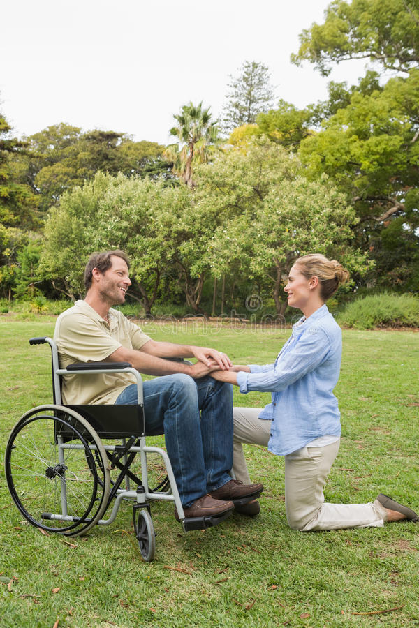 Homem de sorriso na cadeira de rodas com o sócio que ajoelha-se ao lado dele
