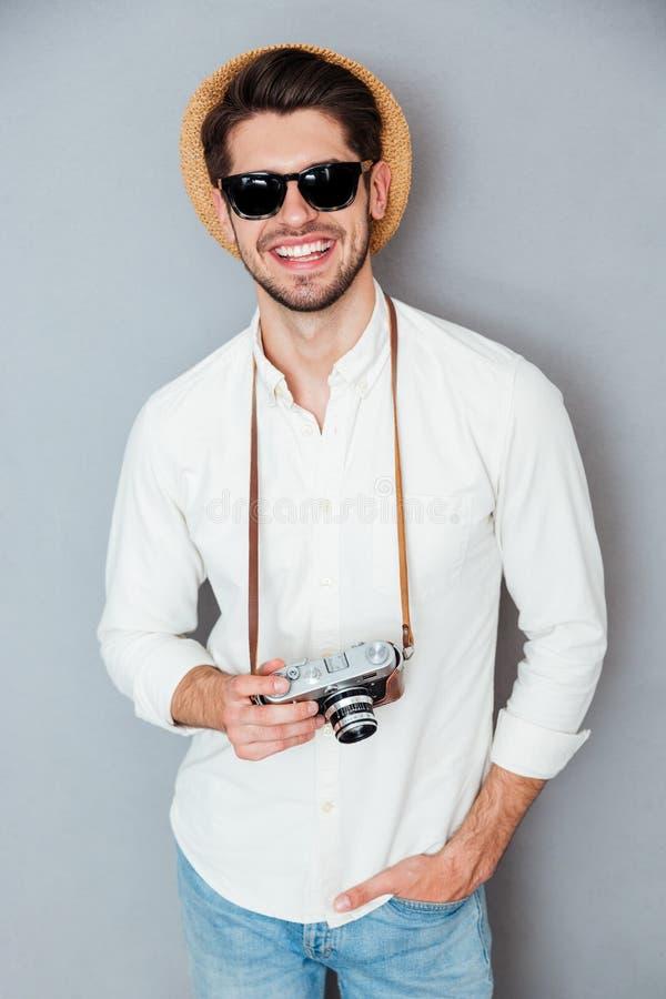 Homem de sorriso no chapéu e nos óculos de sol com a câmera velha do vintage imagem de stock