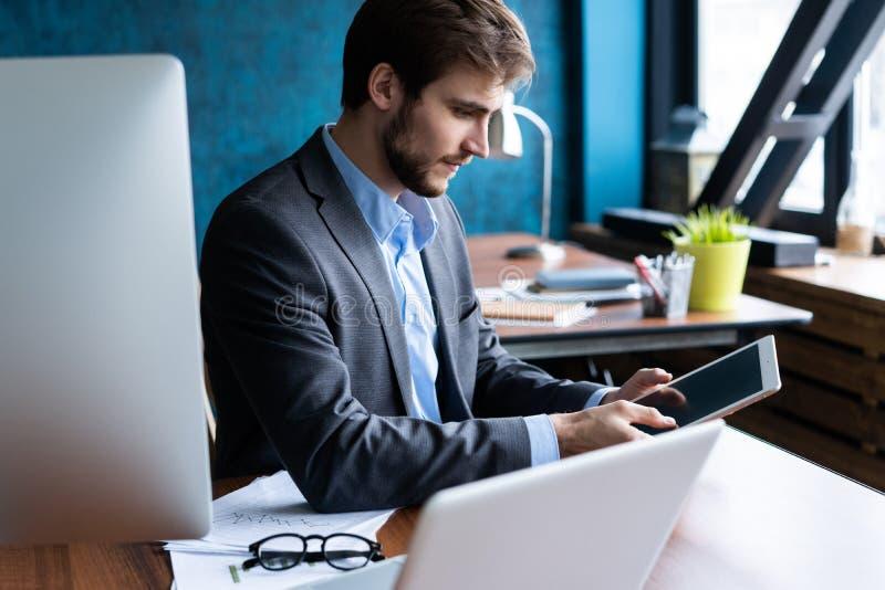 Homem de sorriso no escritório que trabalha na tabuleta digital fotos de stock royalty free
