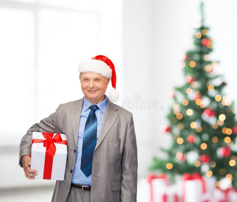 Homem de sorriso no terno e chapéu do ajudante de Santa com presente imagem de stock royalty free