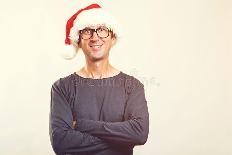 Homem de sorriso nos vidros que vestem o chapéu de Santa Ano novo feliz Tempo do Natal Homem engraçado no chapéu do Natal, isolad imagem de stock royalty free