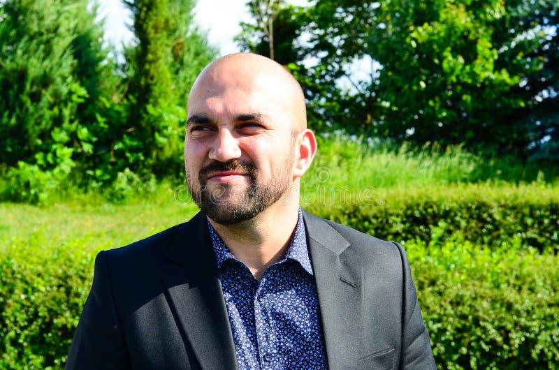 Homem de sorriso novo farpado com traje imagem de stock