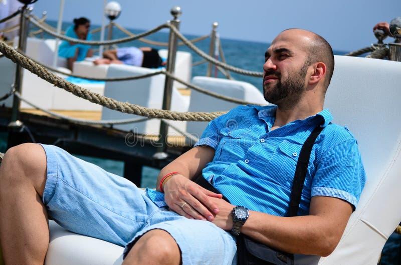 Homem de sorriso novo farpado que aprecia as férias de verão foto de stock