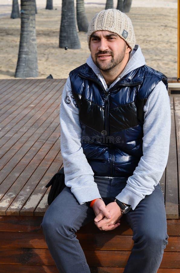 Homem de sorriso novo farpado que senta-se na plataforma de madeira fotografia de stock royalty free