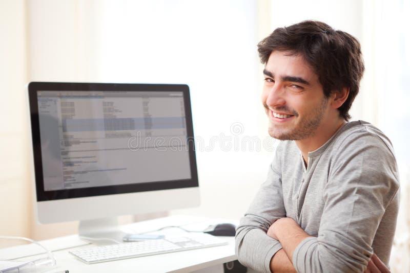 Homem de sorriso novo na frente do computador fotografia de stock