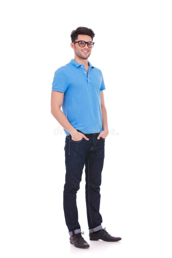 Homem de sorriso novo que está com mãos em seus bolsos foto de stock royalty free