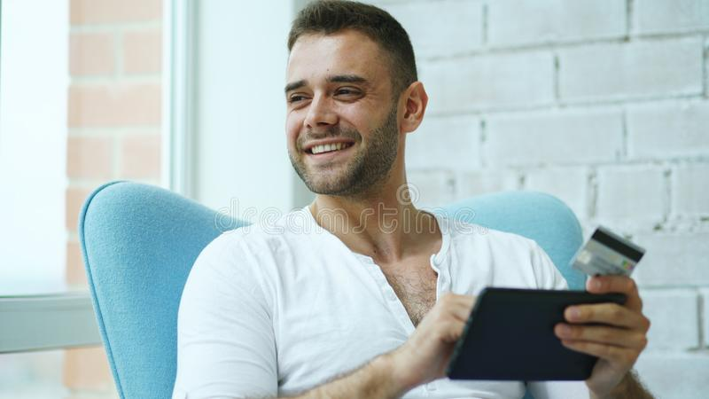 Homem de sorriso novo que faz a compra em linha usando o tablet pc digital que senta-se no balcão em casa foto de stock royalty free