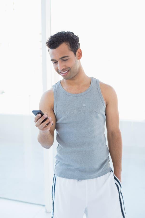 Homem de sorriso novo que olha o telefone celular foto de stock royalty free