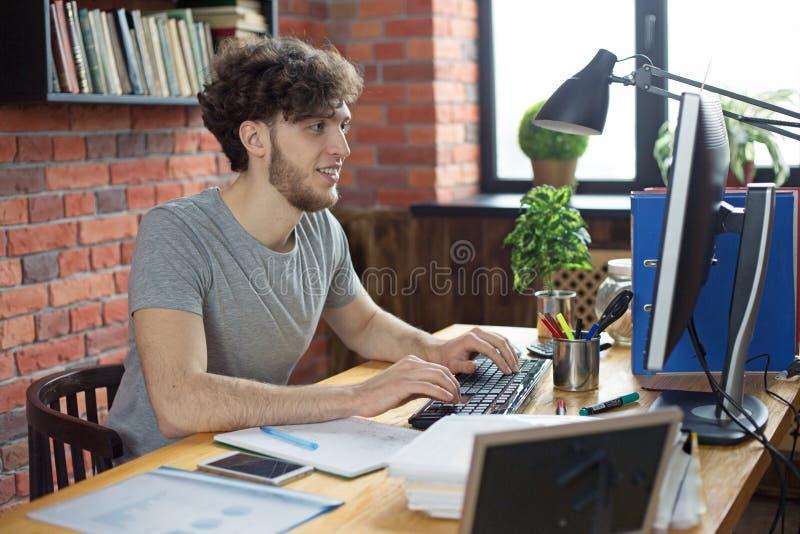 Homem de sorriso novo que trabalha em seu local de trabalho na mensagem de datilografia do computador de secret?ria no teclado no imagens de stock