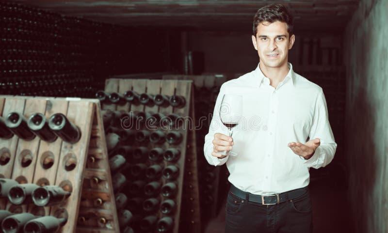 Homem de sorriso proficiente que guarda o vidro do vinho na adega fotografia de stock