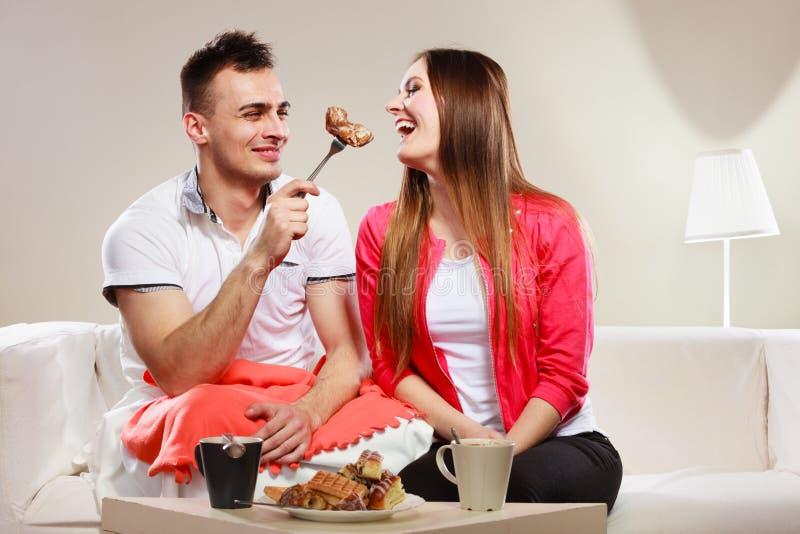 Homem de sorriso que alimenta a mulher feliz com bolo fotografia de stock royalty free