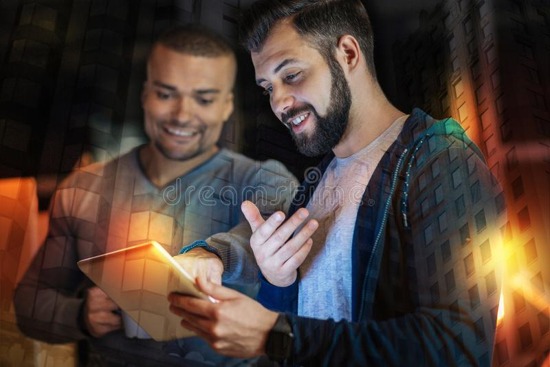 Homem de sorriso que aponta à tela ao olhar as fotos fotografia de stock royalty free
