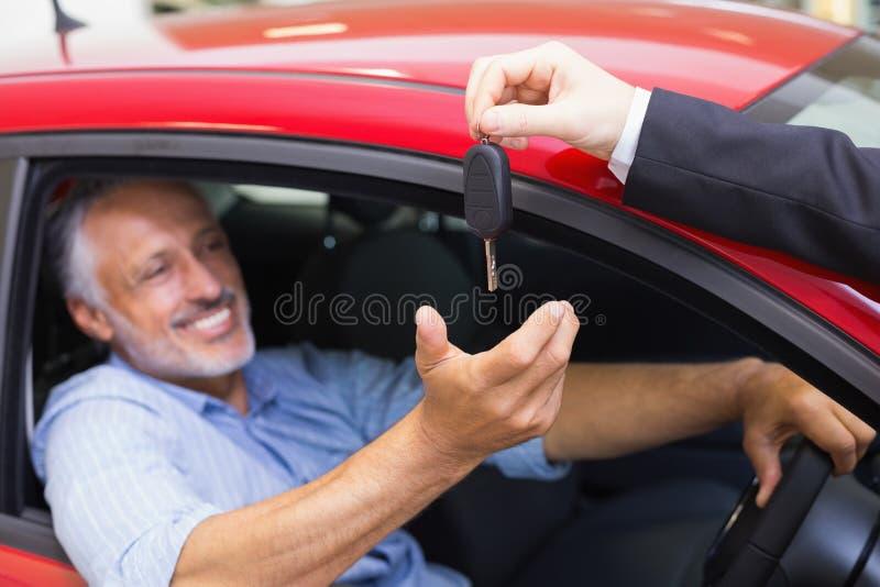 Homem de sorriso que conduz um carro quando vendedor sua chave de doação foto de stock