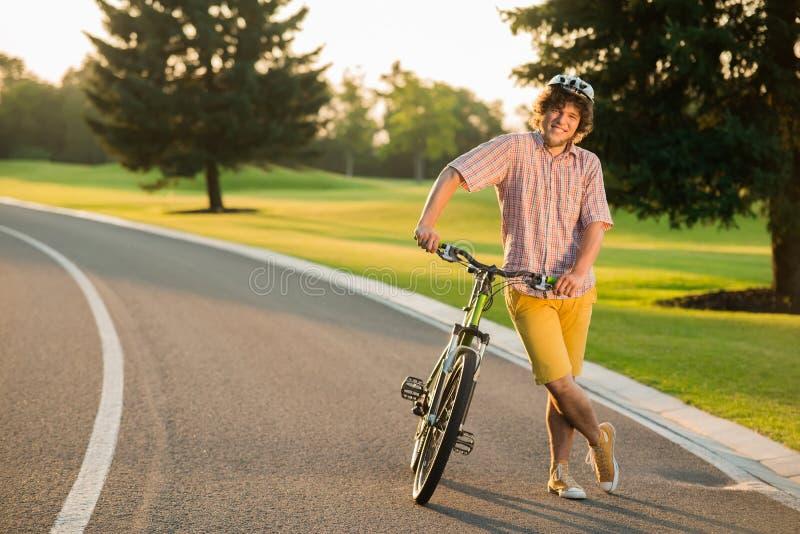 Homem de sorriso que descansa com a bicicleta na estrada secundária imagens de stock royalty free