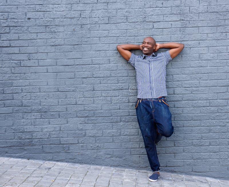 Homem de sorriso que está com suas mãos atrás da cabeça fotos de stock