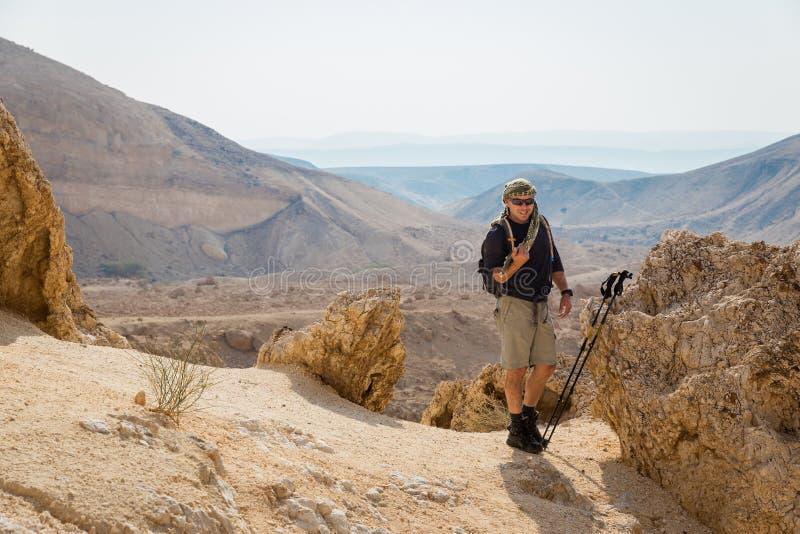 Homem de sorriso que está no deserto de pedra fotografia de stock