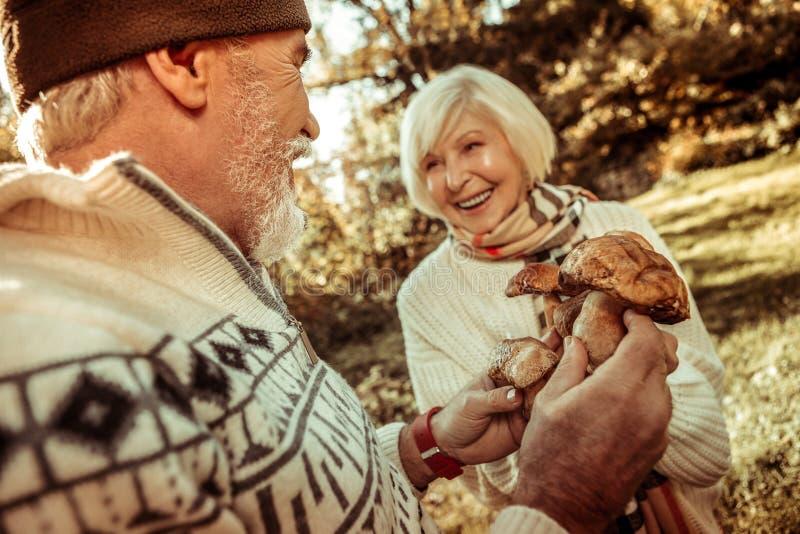 Homem de sorriso que guarda cogumelos e que fala a sua esposa fotos de stock royalty free