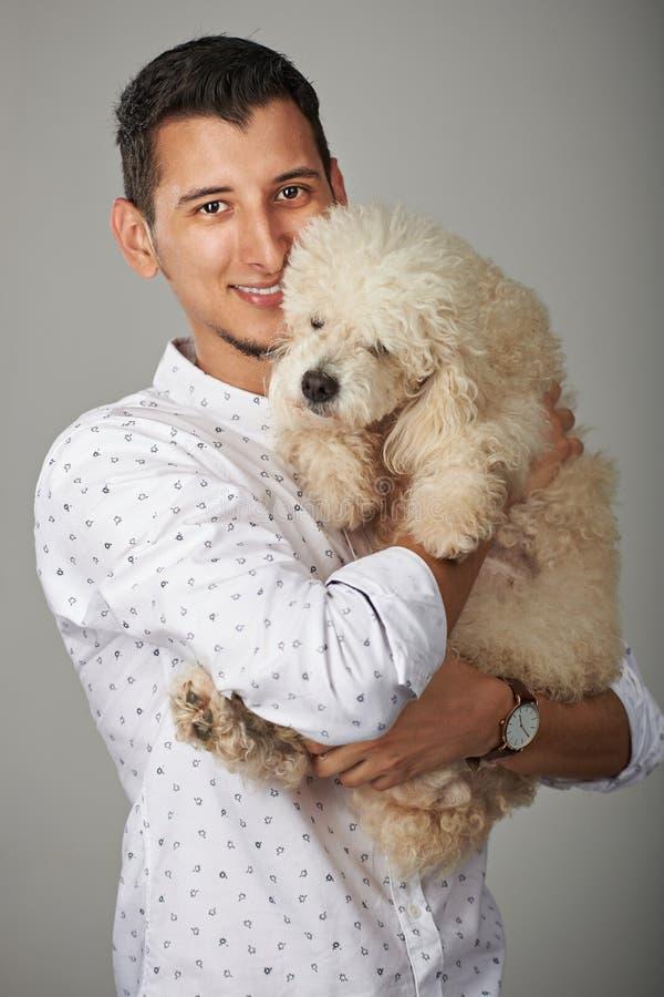 Homem de sorriso que guarda o cão de caniche imagens de stock