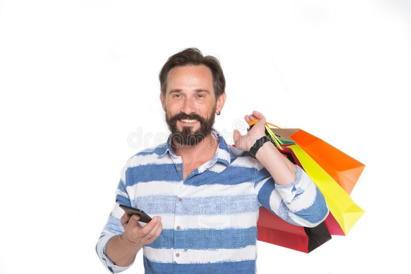 Homem de sorriso que guarda o dispositivo moderno e a colocação de compras sobre o ombro imagem de stock