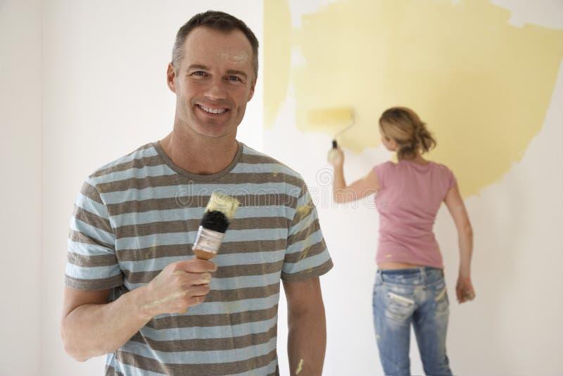 Homem de sorriso que guarda o pincel quando a mulher pintar a parede com rolo imagens de stock